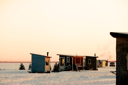 Photo pour Little huts, smoking chimney and trees on a frozen lake, perfect for ice fishing. - image libre de droit
