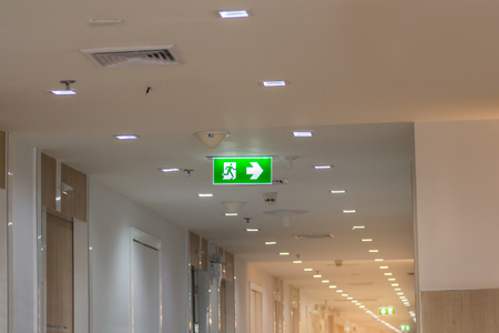 Foto de green emergency exit sign in hospital showing the way to escape  - Imagen libre de derechos