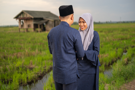 Photo for muslim friends and families visiting home and greet embrace each other celebrating eid mubarak handshaking ask for forgiveness as Asian Muslim culture during with paddy background. Selective focus. - Royalty Free Image