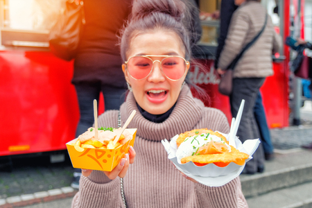Photo pour Young Woman Eating A  French Fries and salmon Street food in Germany - image libre de droit