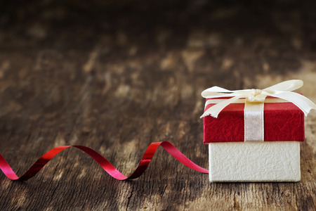 Foto de gift box with a ribbon on the old wooden background. festivals and events. selective focus. copy space background - Imagen libre de derechos