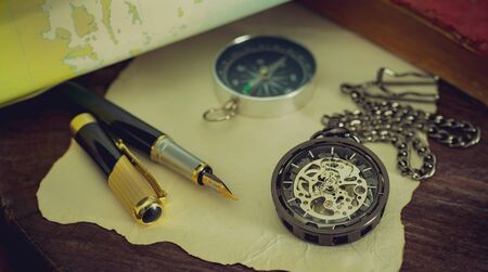Foto de Pocket watch with old books and pen with paper map on the table by the window. Concept of travel planning. - Imagen libre de derechos