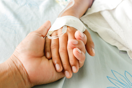 Foto de mother holding child's hand who fever patients have IV tube. - Imagen libre de derechos