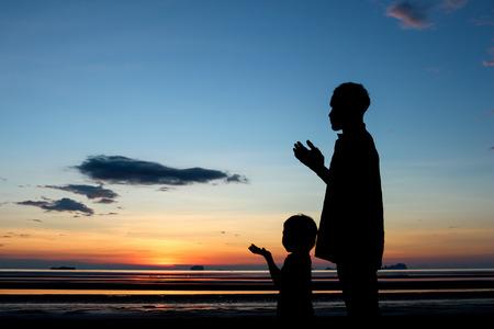 Photo pour Father and son praying under sunset sky. - image libre de droit