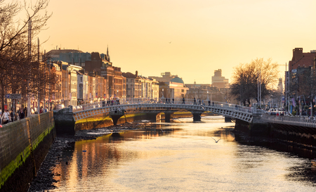 Photo for Ha'penny Bridge and the north banks of the river Liffey in Dublin City Centre view at sunset. Ha'penny Bridge is a pedestrian bridge built in 1816 of cast iron - Royalty Free Image