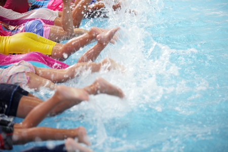 Photo pour group of children at swimming pool class learning to swim - image libre de droit