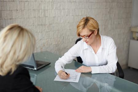 Photo pour Young businesswoman fill out the form in office - image libre de droit