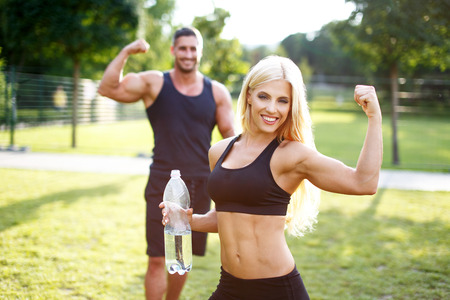 Photo pour Fit couple in nature with bottle of water, blonde woman showing biceps, healthy lifestyle - image libre de droit