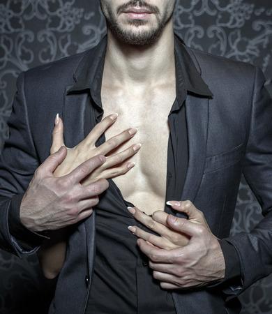 Photo pour Sexy stylish rich man undressed by woman hands closeup - image libre de droit