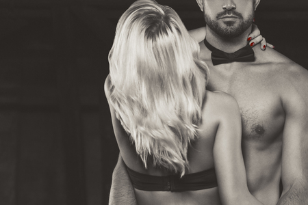 Photo pour Blonde woman embracing sexy man in tux, selective coloring in sepia - image libre de droit