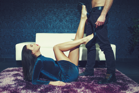 Photo for Sexy woman on carpet playing on man abs by her high heels, sensuality and desire, indoors - Royalty Free Image