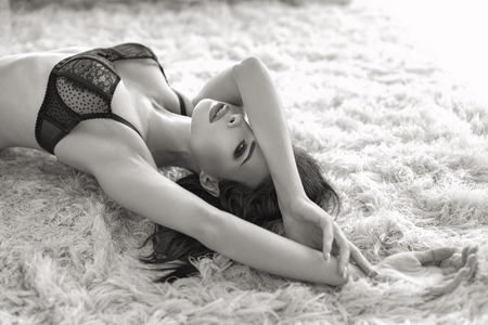 Photo for Sexy young passionate brunette woman in bra posing on carpet, black and white - Royalty Free Image