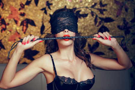 Photo for Sexy woman in blindfold bite whip with red lips, lace eye cover, bdsm - Royalty Free Image