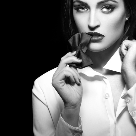 Photo pour Sexy woman bite tie bow at night, sensuality and desire, black and white, isolated - image libre de droit