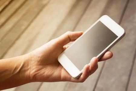 Photo pour lose up of a woman using mobile smart phone,in vintage style - image libre de droit