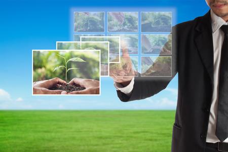 Foto de Business concept of  CSR or Corporate Social Responsibility, businessman select a photo on touch screen for plan csr - Imagen libre de derechos
