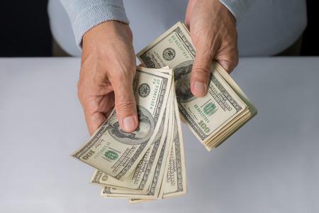 Photo pour Man hand holding money,bribery concept. Business man giving stack of US dollar. - image libre de droit
