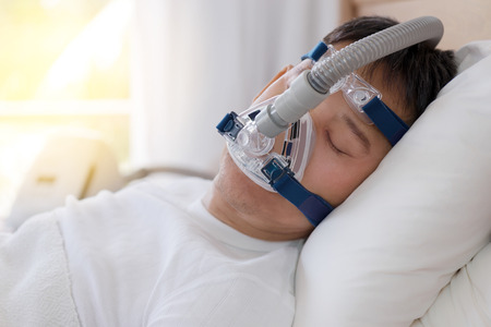 Photo pour Sleep apnea therapy, Man sleeping in bed wearing CPAP mask.Healthy senior man sleeping deeply, happy on his back without snoring - image libre de droit
