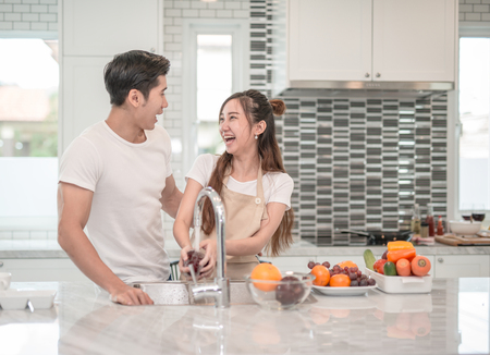 Foto de Happy young Asian woman washing fruit in the sink and handsome man standing next to her - Imagen libre de derechos
