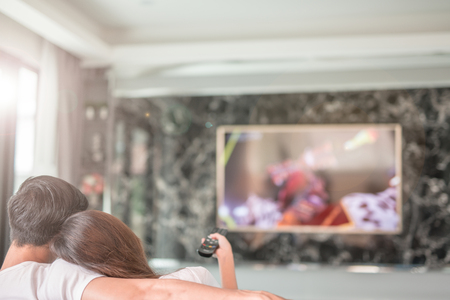 Photo for Rear view of couple watching television in living room - Royalty Free Image