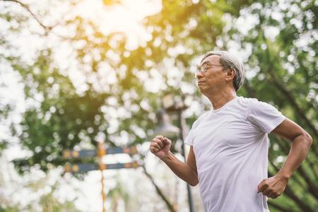 Photo pour Asian senior mature man running Jogging In Park - image libre de droit