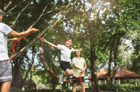 Foto de Summer vacation - happy family playing with skipping rope at green nature park - Imagen libre de derechos