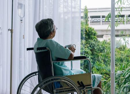 Foto de Senior man in a wheelchair alone in a room looking through the hospital window. Elderly patient - Imagen libre de derechos