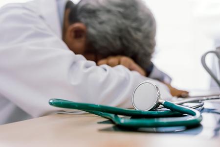 Foto de Senior doctor overwork Tired and sleeping on his deck at medical office - Imagen libre de derechos