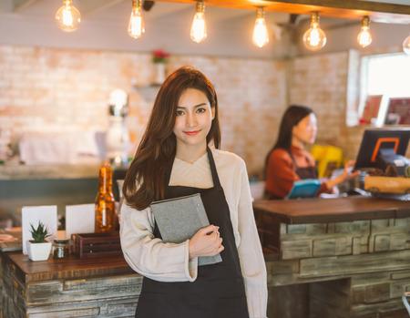 Photo pour Portrait of Asian girl waitress holding menu wearing apron and standing in coffee shop. - image libre de droit