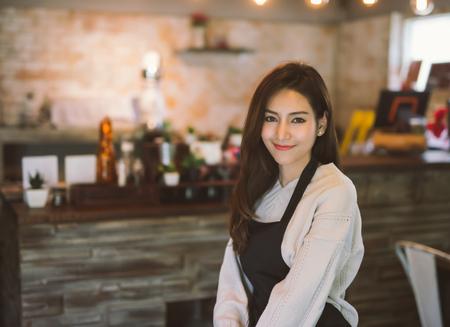 Foto de Portrait of Asian girl waitress wearing apron and standing in coffee shop. - Imagen libre de derechos