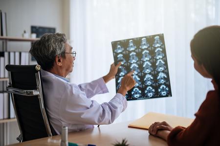 Foto de Senior asian doctor examine MRI picture explain to patient - Imagen libre de derechos