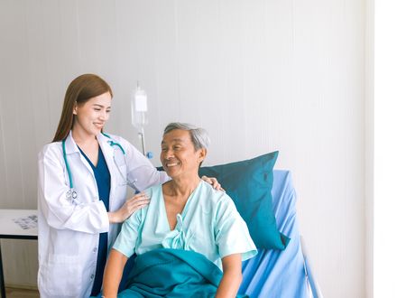 Photo for Beautiful Asian doctor taking care of senior patient in hospital bed - Royalty Free Image