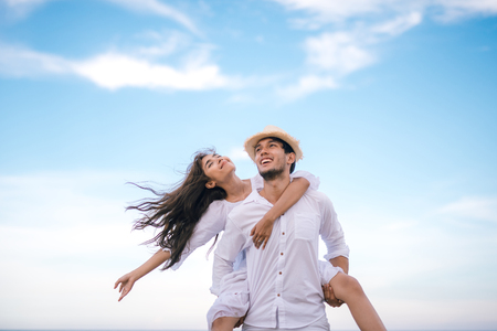 Photo pour Happy relaxing couple in love on beach summer vacations. Joyful girl piggybacking on young boyfriend having fun. - image libre de droit
