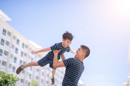 Photo pour Happy father and son playing together having fun outside the Condominium or apartment building. - image libre de droit