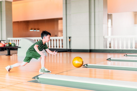 Photo for Cute child with ball in bowling club - Royalty Free Image