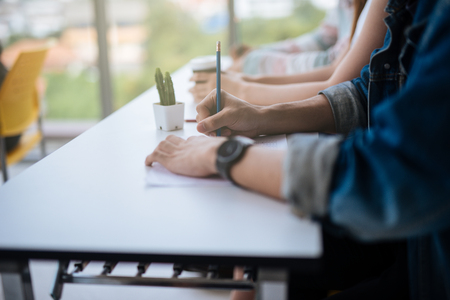 Photo for Closeup of hands students sitting on lecture and having test holding pencil writing on paper answer sheet .Testing education training university learning and people concept - Royalty Free Image