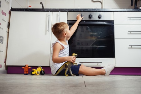 Photo pour accident prevention. The child unattended playing in the kitchen with a gas stove. without retouch - image libre de droit