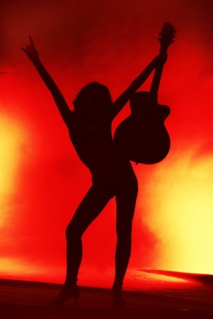 Photo for Woman with guitar silhouette on red background  - Royalty Free Image