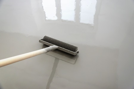 Photo pour Self-leveling epoxy. Leveling with a mixture of cement floors with a roller. - image libre de droit