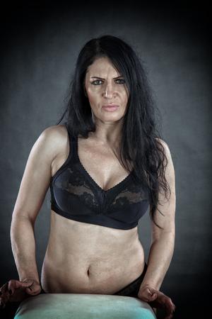 Foto de portrait of an adult angry brunette woman in black bra on a gray background studio - Imagen libre de derechos