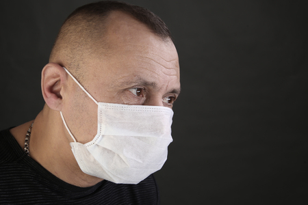 Photo for closeup portrait man in a black T-shirt and a medical mask on a gray background studio - Royalty Free Image