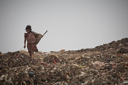 Foto de New Delhi, India, July 2009.Girl in a garbage dump outside the city. - Imagen libre de derechos