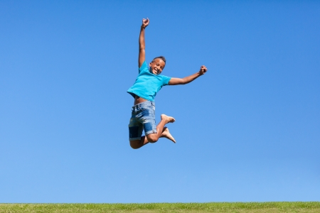 Photo pour Outdoor portrait of a cute teenage black boy jumping over a blue sky - African people - image libre de droit