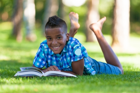 Photo for Outdoor portrait of student black boy reading a book - African people - Royalty Free Image