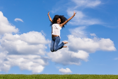 Outdoor portrait of a smiling teenage black girl jumping over a blue sky - African people