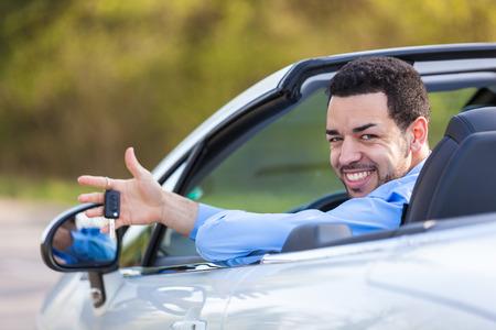 Foto de Young black latin american driver holding car keys driving his new car - Imagen libre de derechos