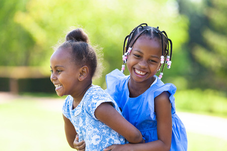 Photo pour Outdoor  portrait of a cute young black sisters laughing - African people - image libre de droit