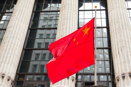 Photo pour Chinese flag floating in front of a goverment building - image libre de droit