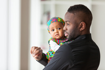 Photo pour Young african american father holding with her baby girl - image libre de droit
