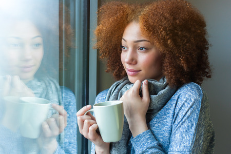 Photo for Black African American teenage girl drinking a hot beverage and looking through a window - Royalty Free Image